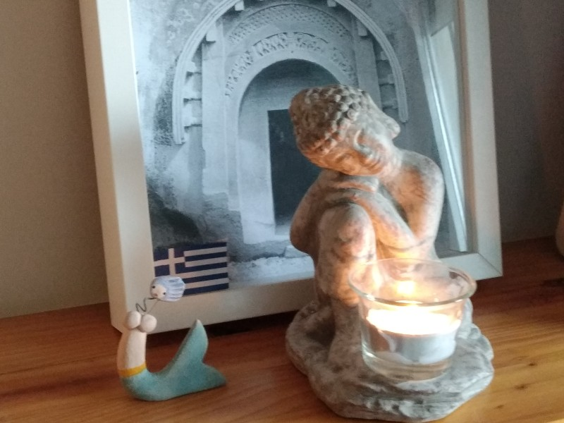 Domestic composition with a small Buddha before a photo of the entrance to the cave of Lomas Rishi, a Greek civil ensign and a mermaid